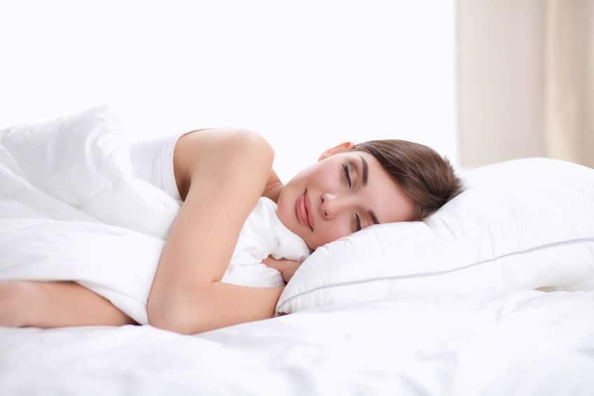 Jeune fille brune couché dans draps blanc